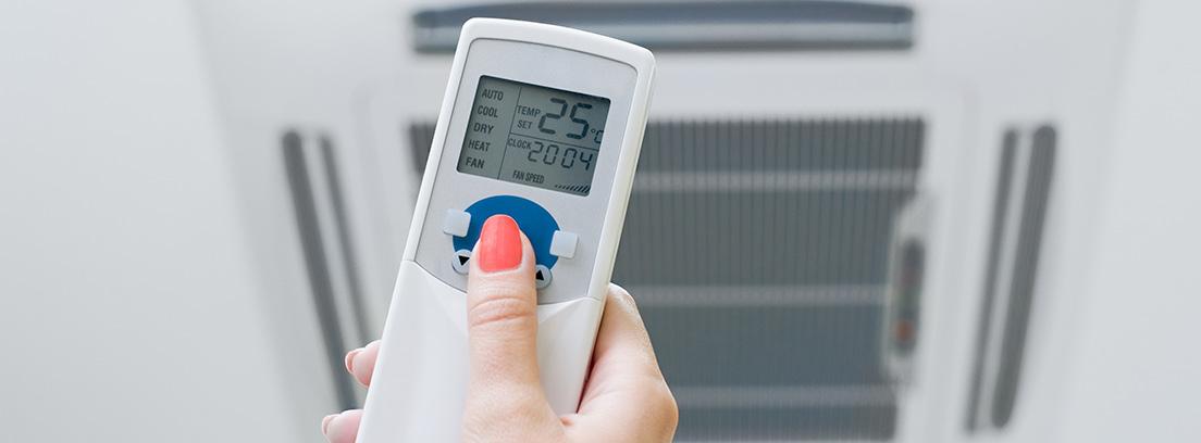 Mano sujetando un mando de temperatura de un aire acondicionado