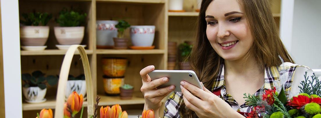 Mujer mirando pantalla del móvil delante de cesta de tulipanes naranjas