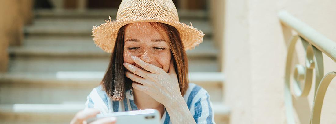Mujer con sombrero y mano sobre la boca mira pantalla móvil que sostiene en su mano