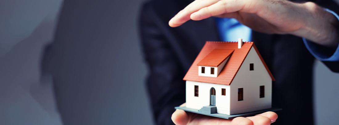 Maqueta de casa entre las manos de una persona