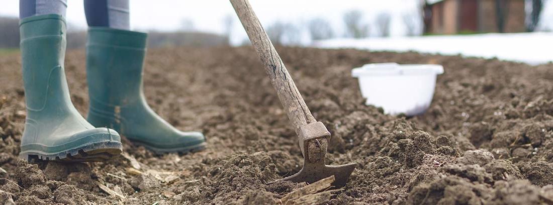 Persona con botas de goma trabajando tierra de huerto