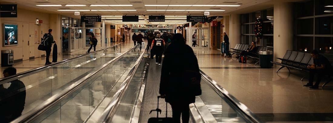 Pasarela rápida de aeropuerto con una persona arrastrando maleta por ella.