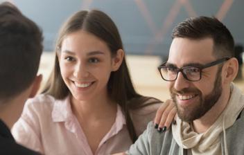 Hombre y mujer sonrientes sentados a una mesa frente a otro hombre
