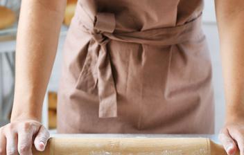 Mujer estirando masa con rodillo de madera.