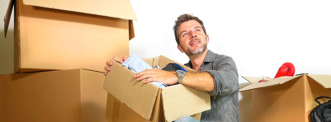 Hombre sentado en el suelo con caja de mudanza encima y a su alrededor.