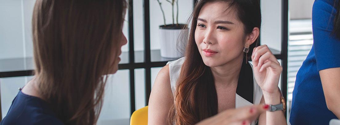 Mujer delante de ordenador junto a otra que la mira