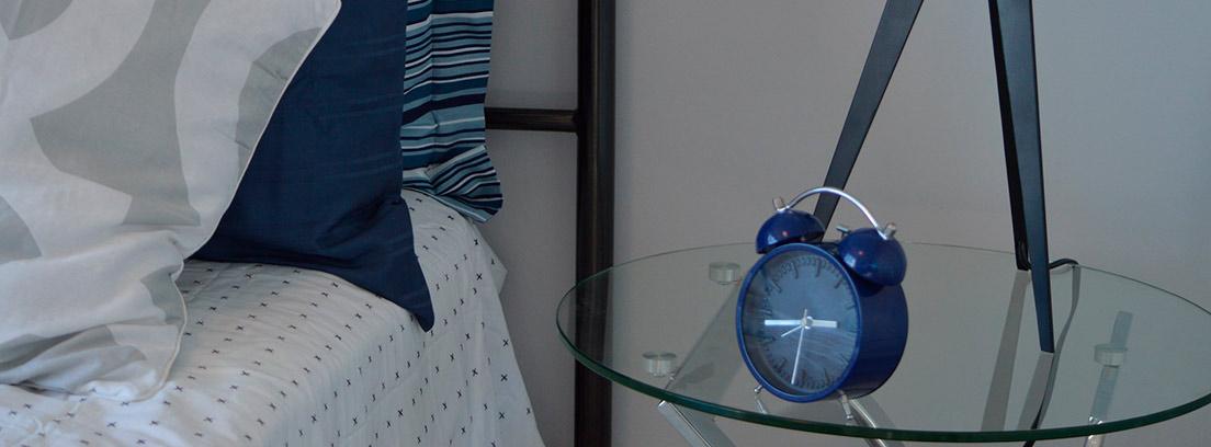 Cama y mesilla de forja y cristal en dormitorio con tonos azules y blancos