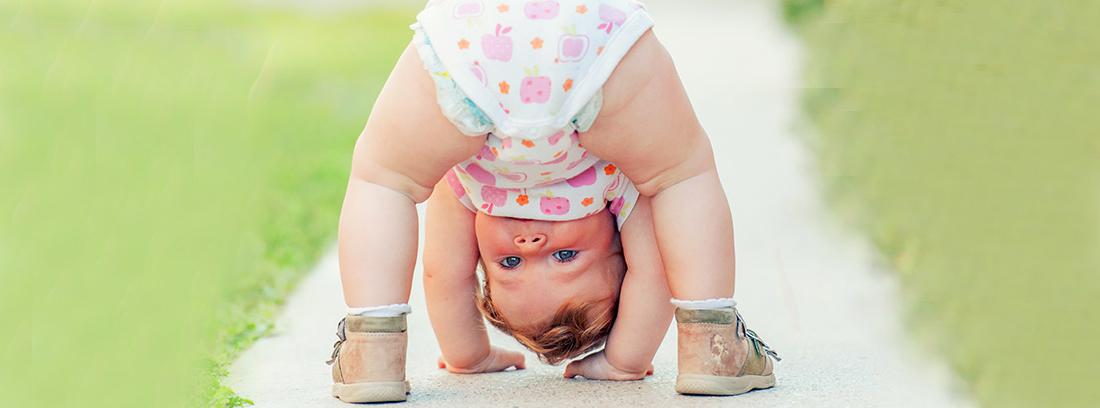 Bebé poniendo las manos en el suelo, en la calle
