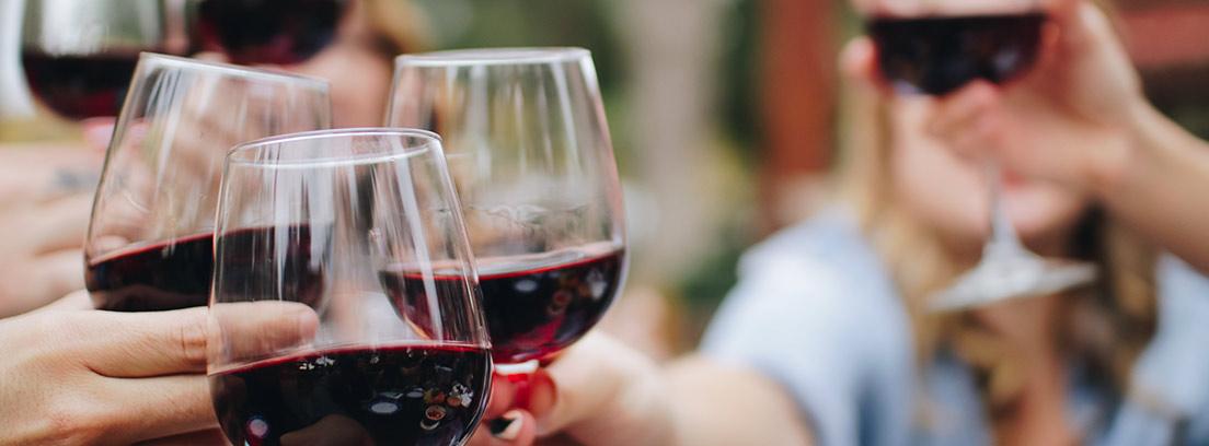 Varias copas con vino tinto sostenidas en un brindis.