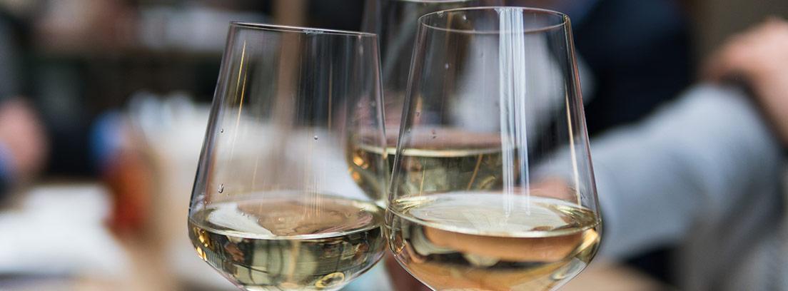 Tres copas llenas de vino blanco sostenidas en un brindis