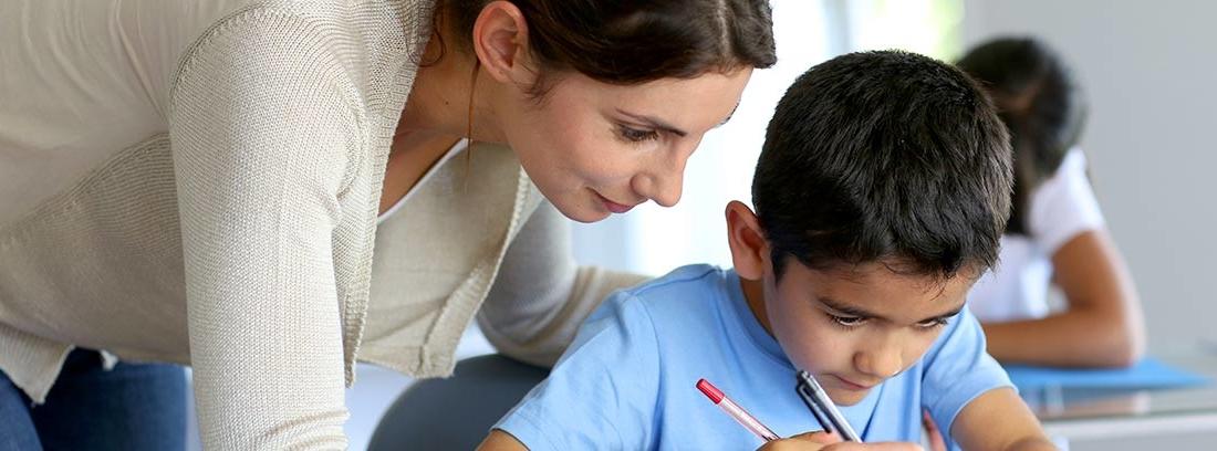 Mujer detrás de niño sentado en pupitres y escribiendo con él.