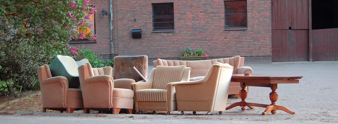 Sofás y sillones usados tirados en la calle