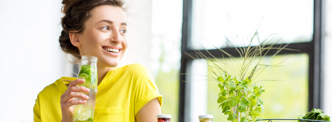 Mujer vestida con ropa de deporte bebiendo agua de una botella de cristal