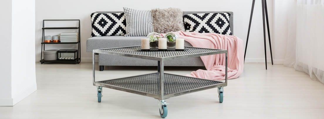 mesa de centro gris con ruedas delante de un sofá