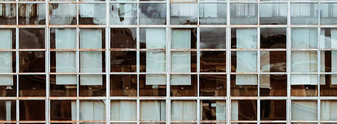 Exterior de un edificio con ventanas grandes y paneles en ellas