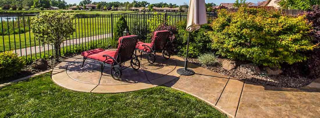 Hamacas en un jardín con el suelo pavimentado con hormigón impreso