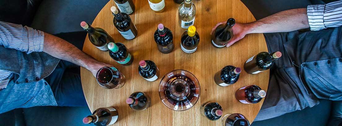Vista aérea de mesa redonda de madera con botellas y copas de vino.