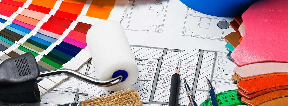 Planos de una casa, pinceles, papeles con gamas cromáticas y otros materiales de decoración