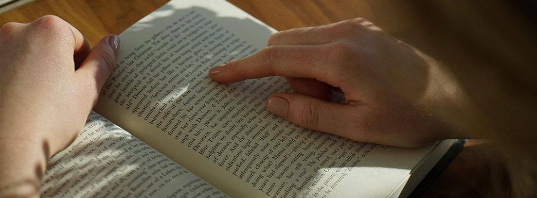 Persona con mano sobre un libro abierto y señalando una línea.
