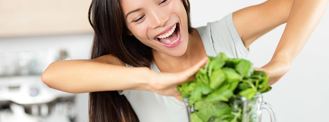 Mujer sonriente introduciendo verduras en una batidora