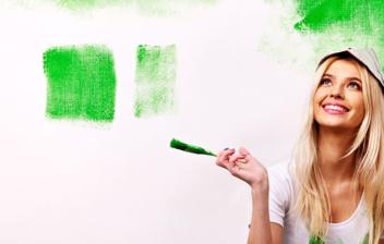 Mujer sentada en suelo con brocha delante de pared verde fluorescentes y botes de pintura.