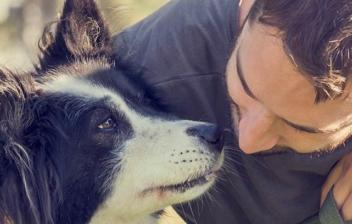 Hombre abraza a su perro agachado junto a él