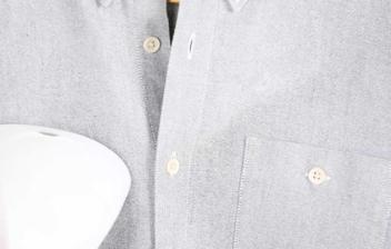 Mano sosteniendo una plancha vertical sobre una camisa