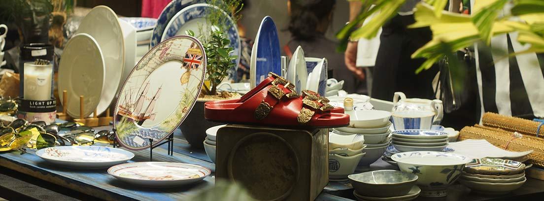 Puesto de mercadillo con platos, tazas y otras cosas antiguas