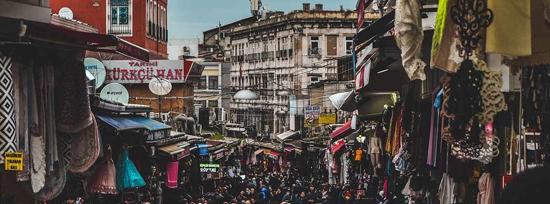 Vista de calle con mercadillo y personas paseando por él.