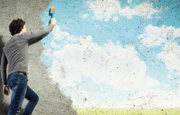 Hombre en una escalera haciendo una pintura 3D en una pared