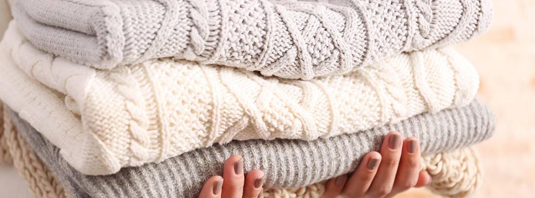 Manos sujetando varias prendas de lana dobladas