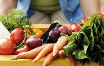 Mujer llevando una caja de madera llena de verduras frescas