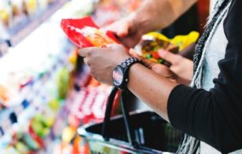 manos cogiendo un producto con el supermercado de fondo