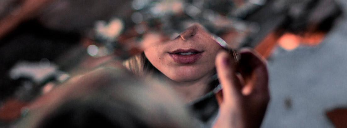 Mujer sosteniendo un espejo roto en el que se refleja su boca