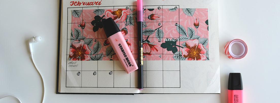 Agenda abierta con hojas personalizadas y subrayadores rosas y rotuladores.