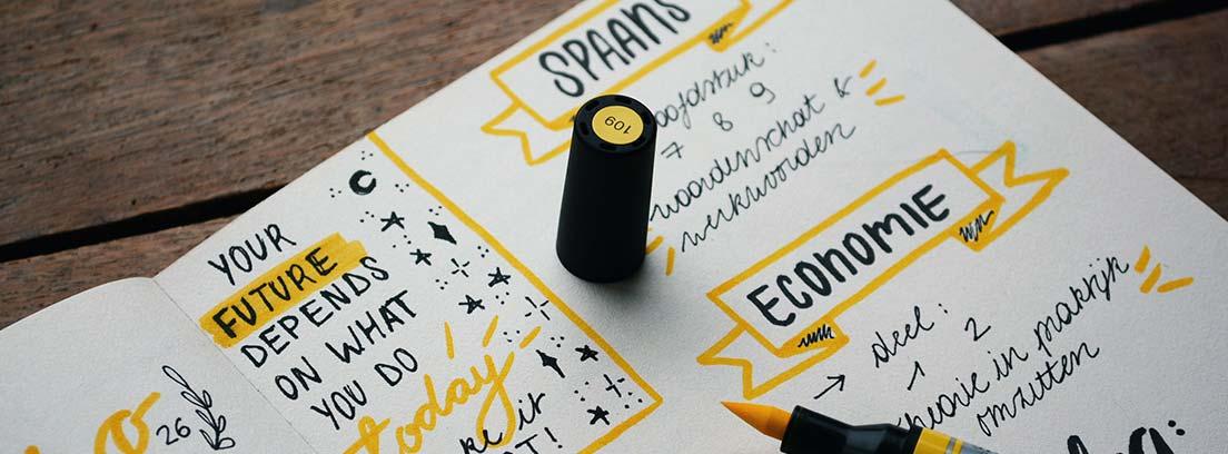 Rotulador amarillo sobre cuaderno con mensajes y rotulaciones en negro y amarillo.