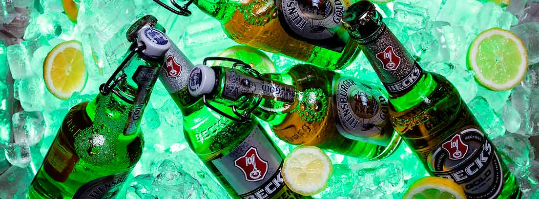 Botellas de cerveza en un cubo con hielo y limón