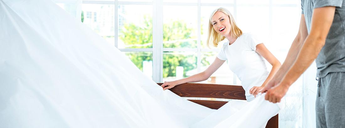 Hombre y mujer retirando la ropa de cama