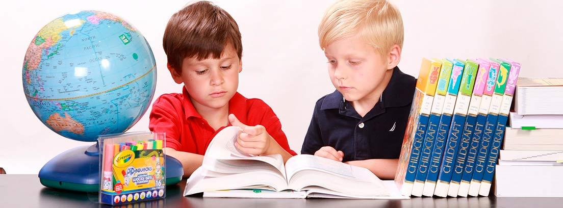 Dos niños revisando un libro en una mesa junto a un globo terráqueo