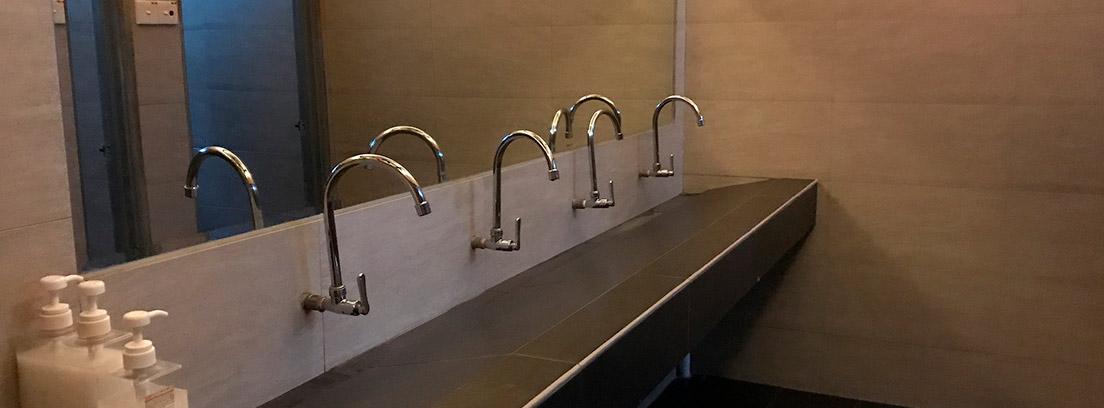 Varios grifos sobre un lavabo de azulejo