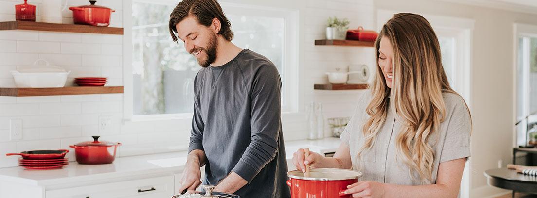 Hombre y mujer delante de una cocina con ollas y alimentos.