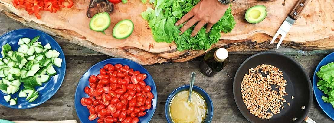 Tabla de madera con verduras y junto a cuencos con más alimentos naturales.