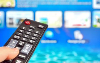 Mano sosteniendo un mando y seleccionando contenidos en una Smart TV