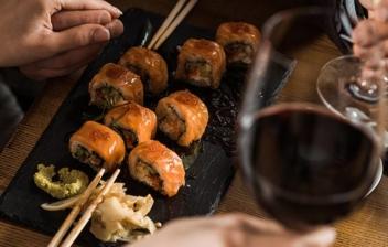 pareja tomando sushi acompañado de dos copas de vino
