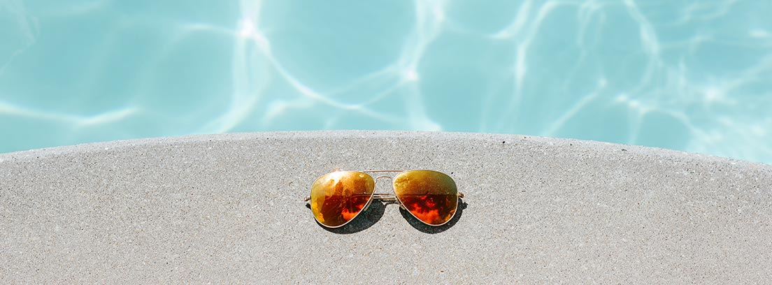 Vista cenital de gafas de sol sobre el bordillo de una piscina con agua cristalina