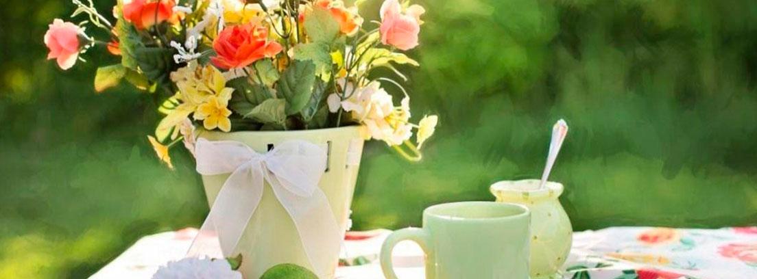 Maceta con flores, taza y azucarero sobre mantel de picnic.