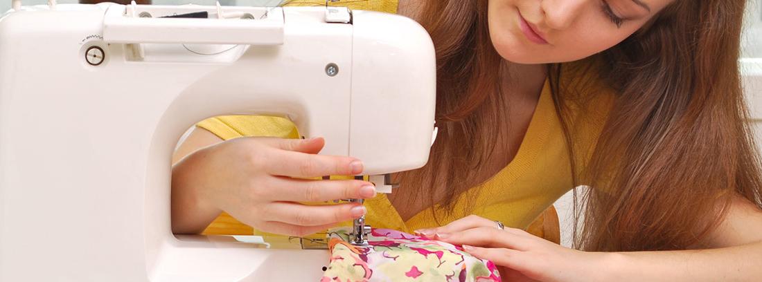 Mujer sujeta tela con una mano y máquina de coser con otra.