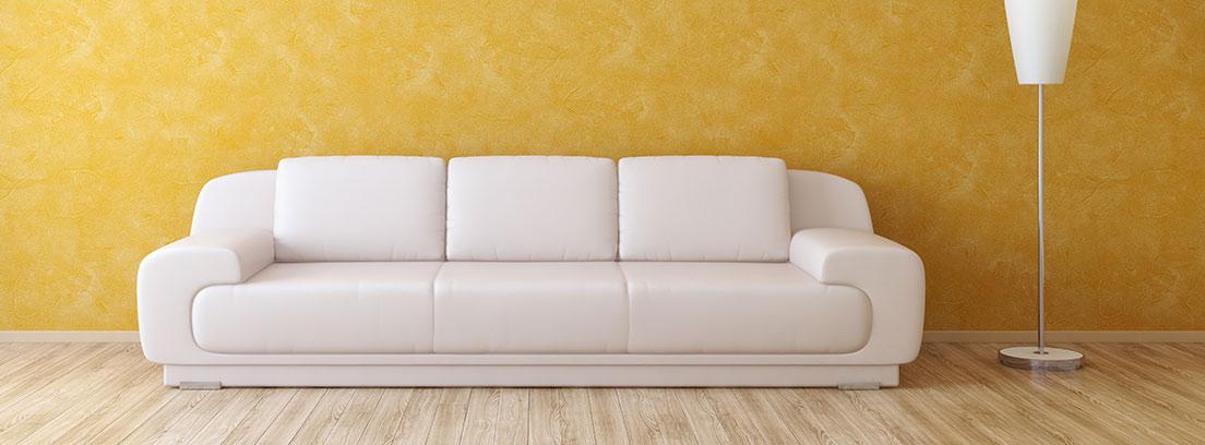 Sofá blanco sobre una pared amarilla con técnica de esponjado