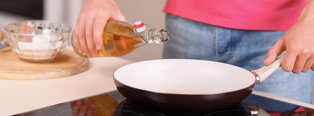 Mujer añadiendo aceite de una botella a una sartén