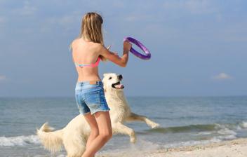 mujer jugando con su perro en la playa